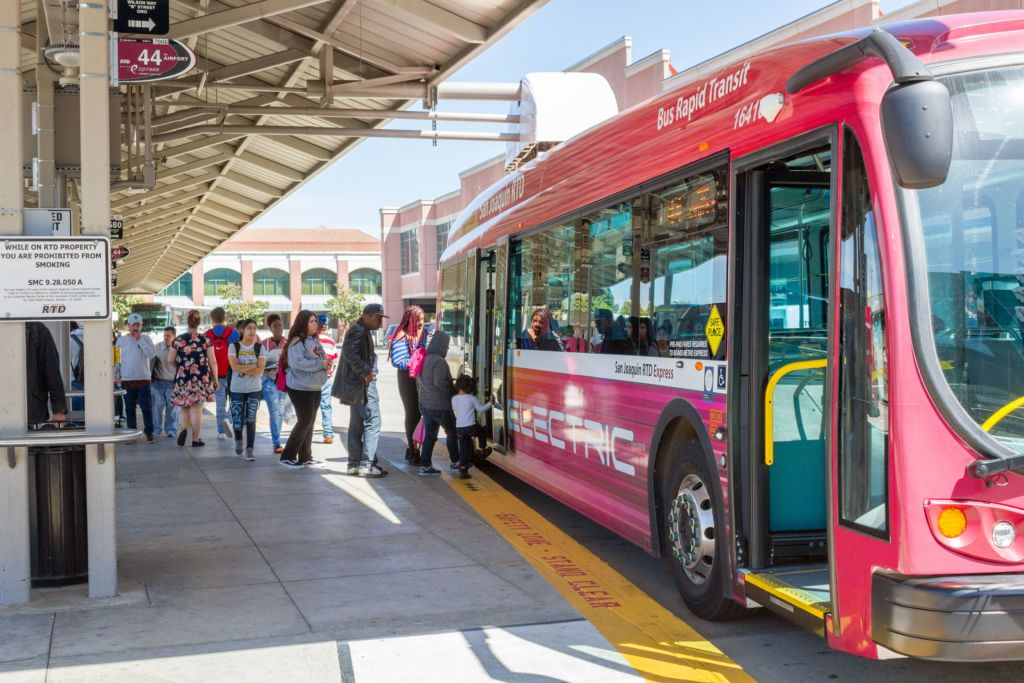Photo of passengers loading a electric BRT express bus at the Downtown Transit Center