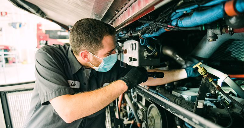 RTD mechanic looking into bus with a flashlight