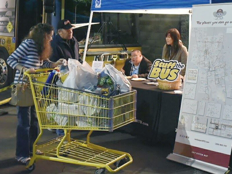 Food donors using the Stuff the Bus drop-off cart station.