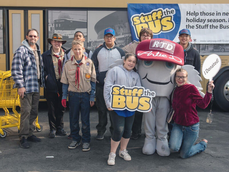 A scout troop and kids meeting Artie at Stuff the Bus.