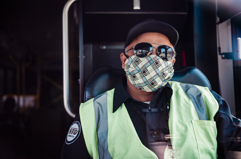 Photo of male RTD operator. He's wearing a baseball cap, sun glasses, and a face mask. He's sitting inside the buss at the wheel.